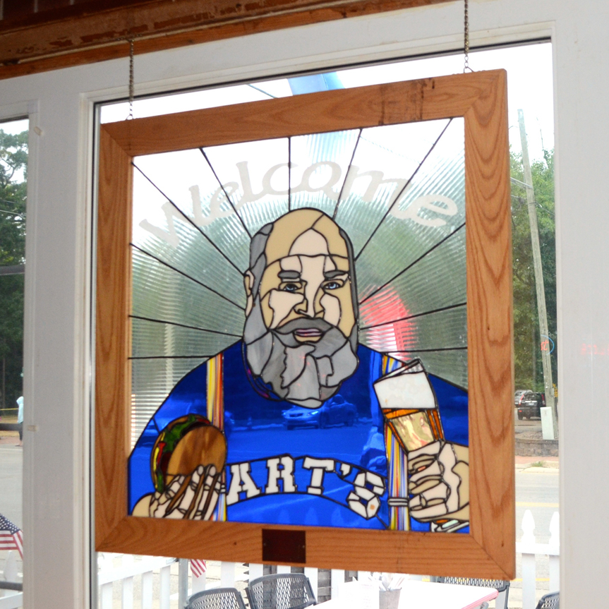 Art's Taverm stained glass window hanging depicting owner Tim Barr with beer in one hand and a burger in the other