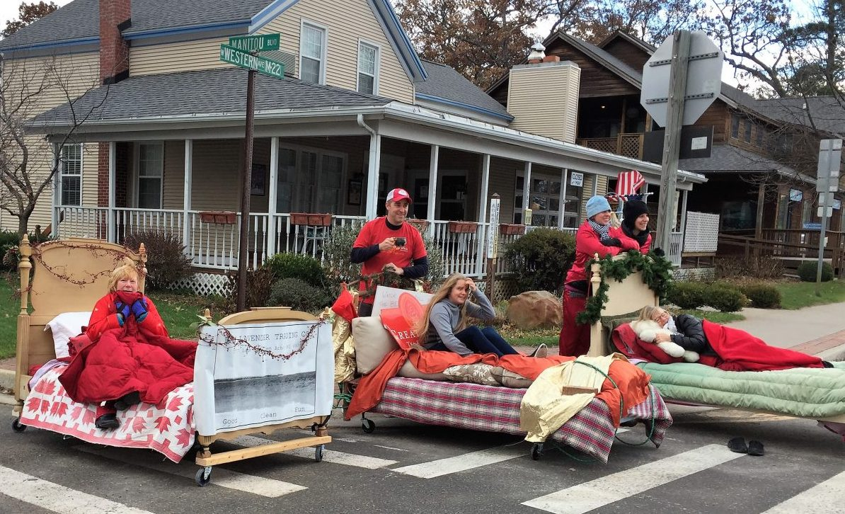 people on street corner riding beds in parade