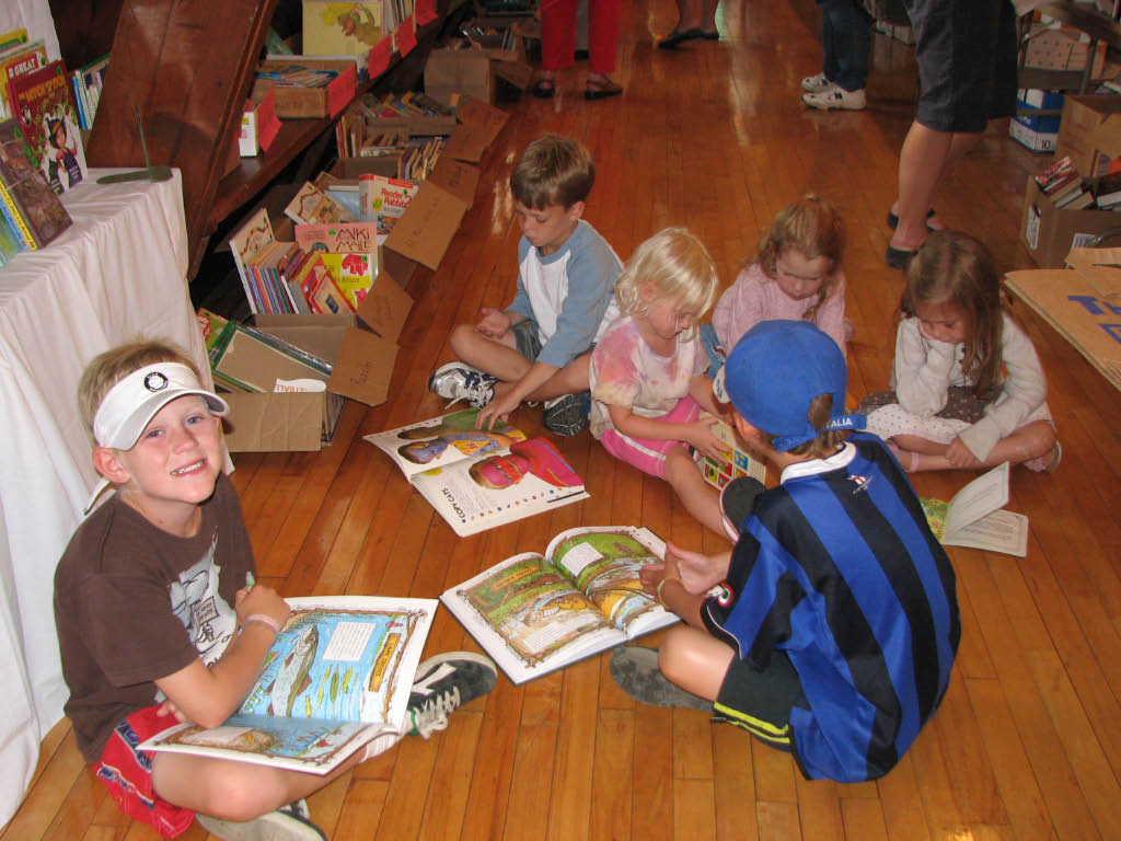 kids reading at book sale in town hall