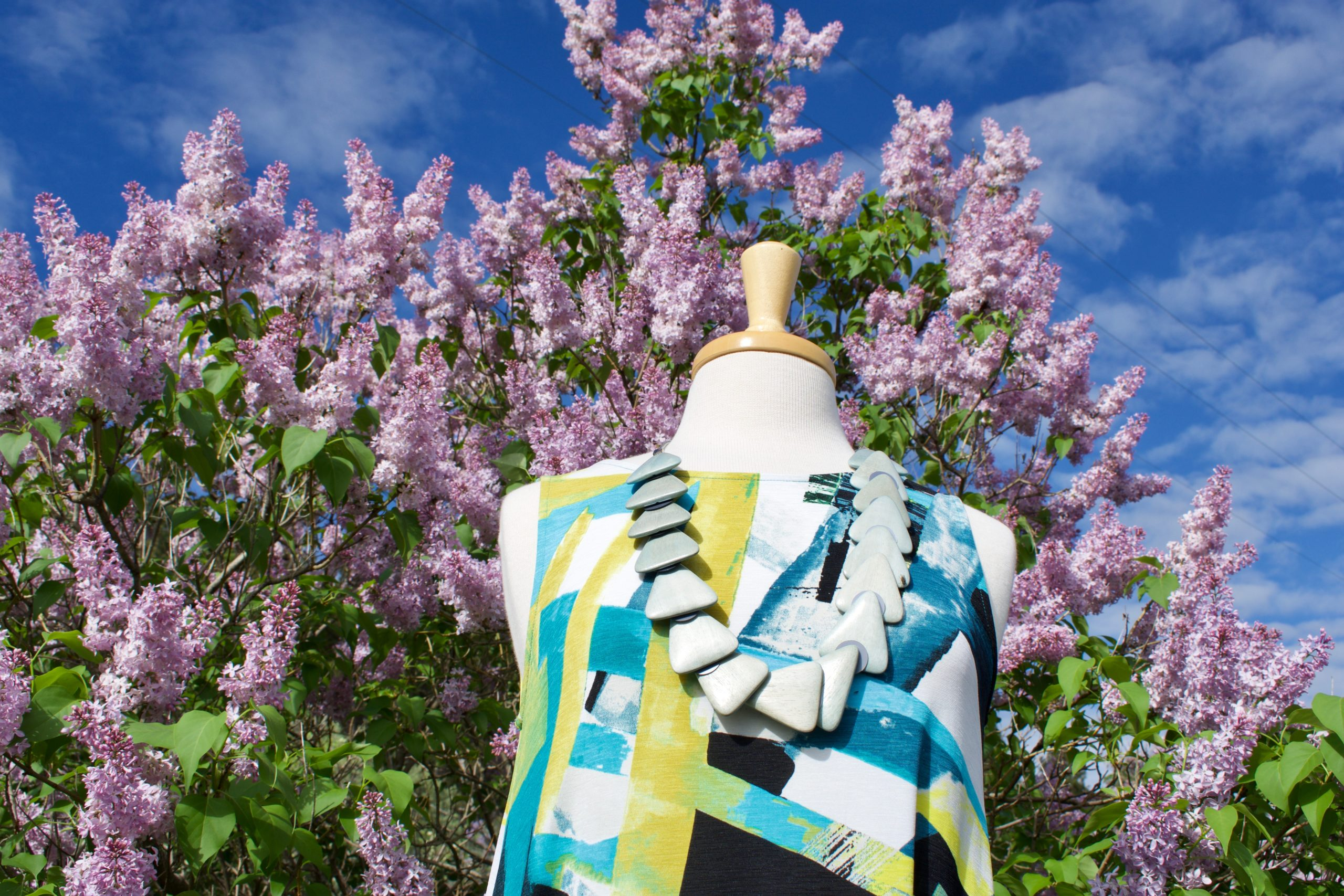 dress on mannequin in front of lilac bush