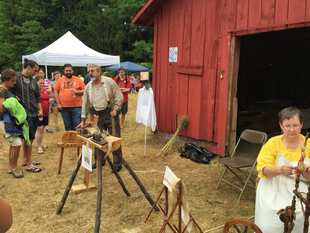 People watching a woodworking demonstration at the historic Port Oneida Rural Fair in the Sleeping Bear Dunes National Lakeshore