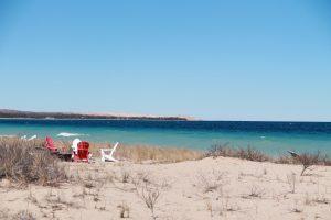 four plastic adirondack chairs at a sugar sand Lake Michigan beach in Glen Arbor