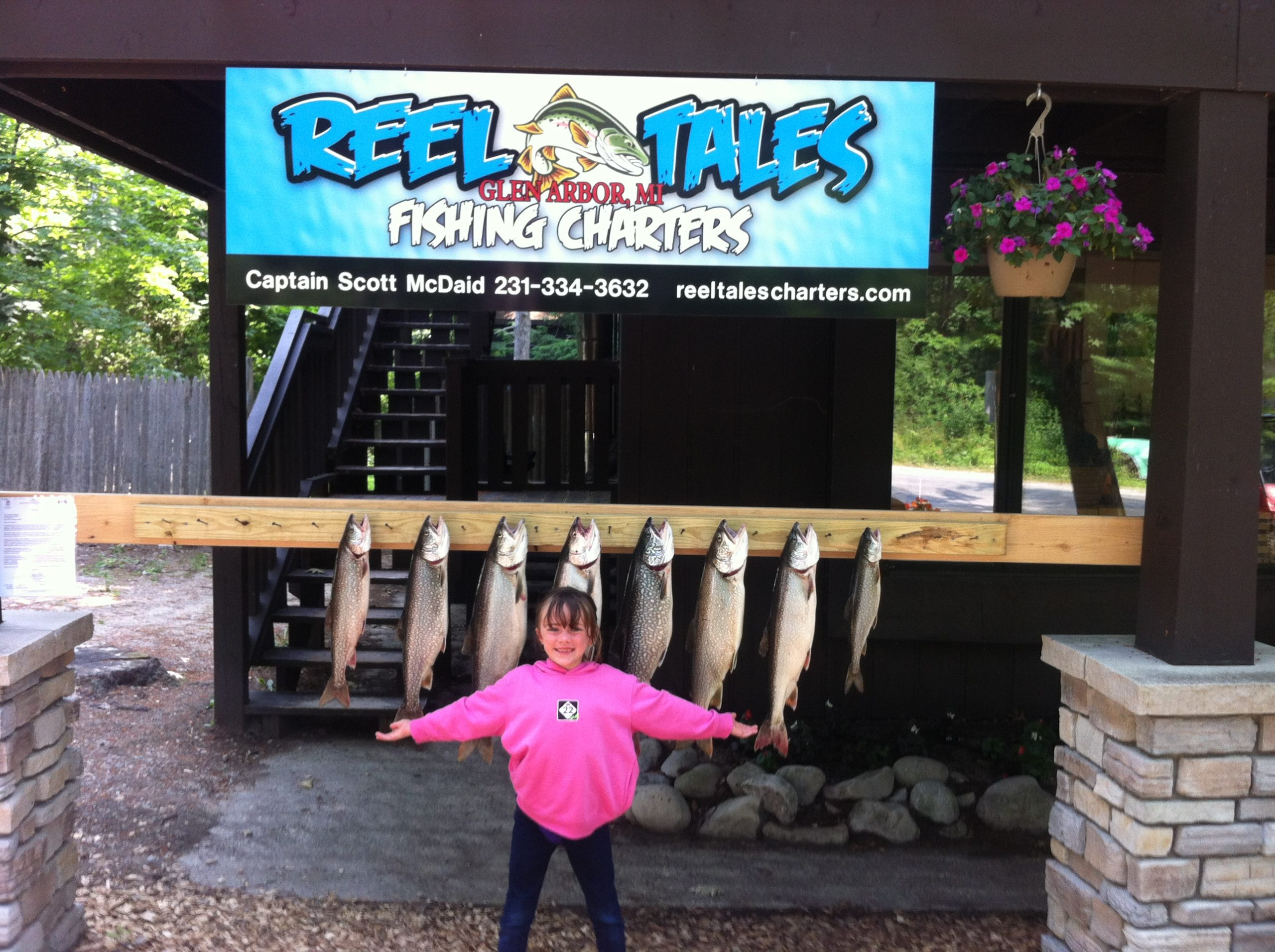 child poses in front of fresh caught fish