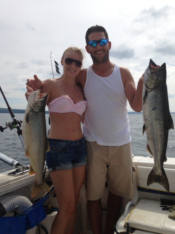 young couple hold fresh catches on fishing charter boat