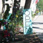 blue sandwich open sign by sidewalk