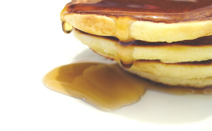stack of pancakes dripping with syrup
