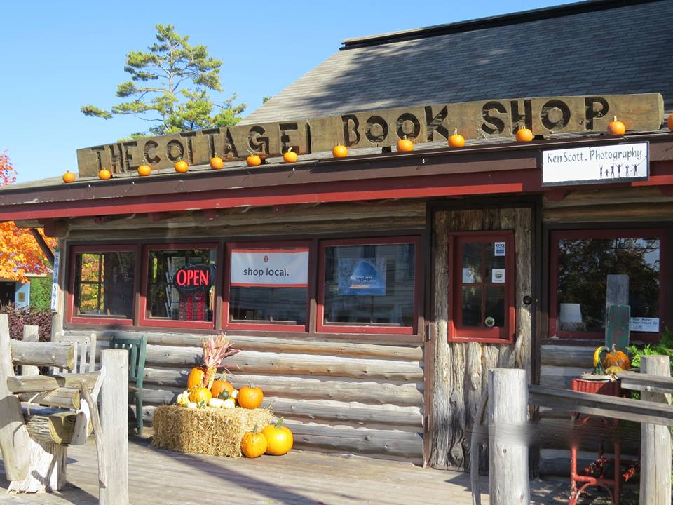 The Cottage Book Shop in the fall with pumpkins and bundles of hay in front