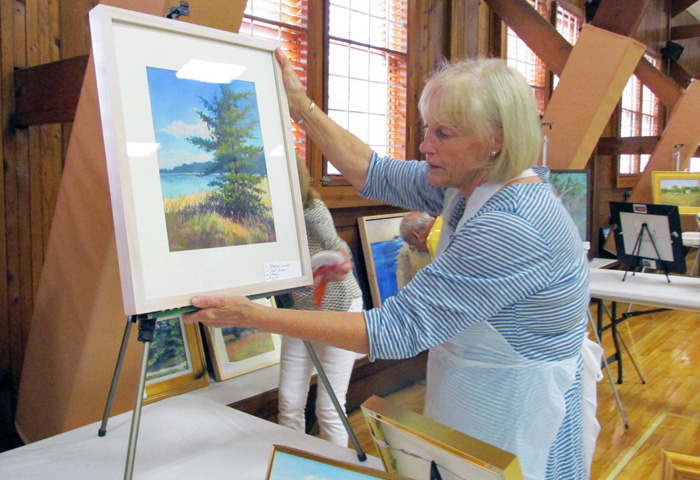 artist Cherrie Stege sets up art for sale after the Art Center's Plein Air Weekend