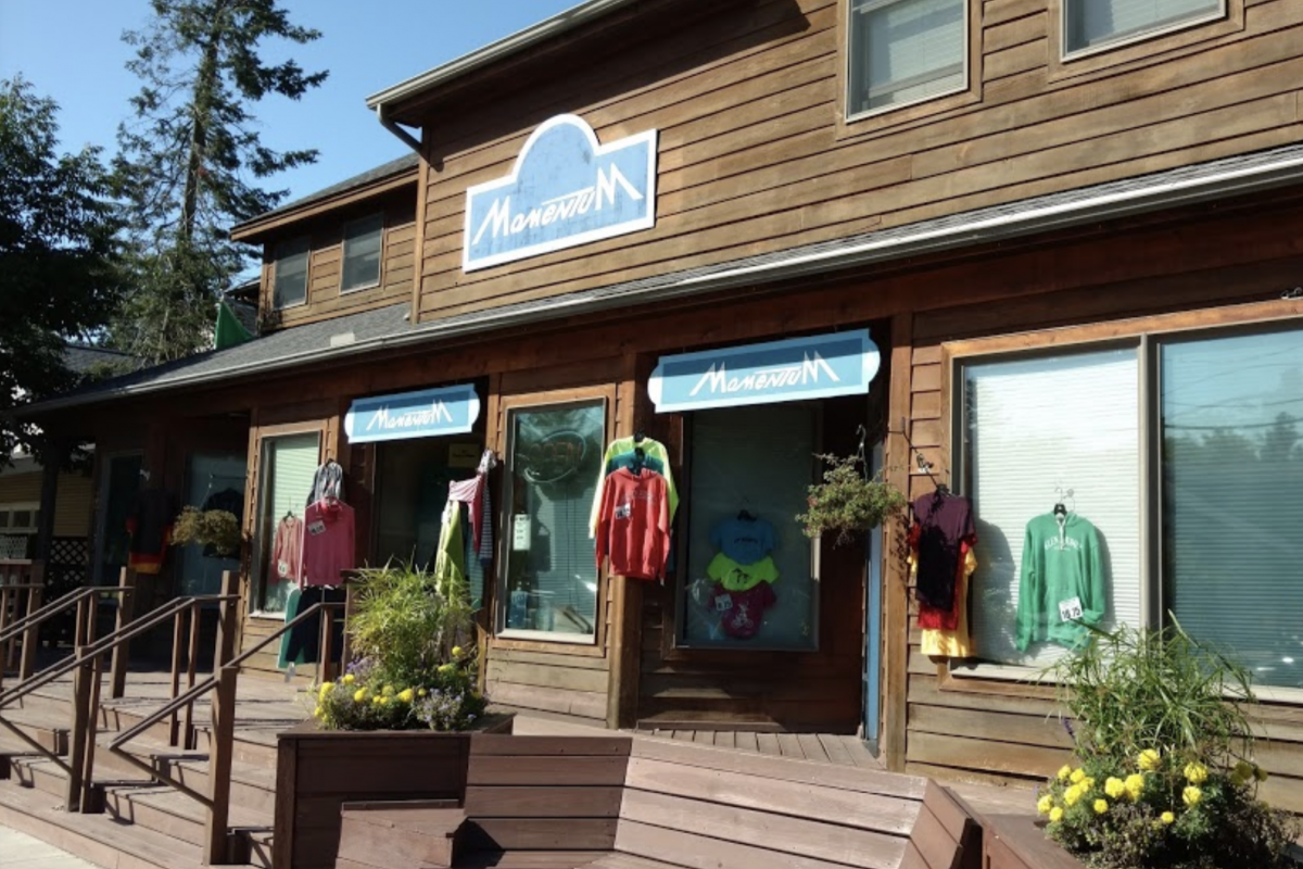 Storefront of Momentum of Glen Arbor, a shop selling casual ware, with bright flowers blooming in the planters in front
