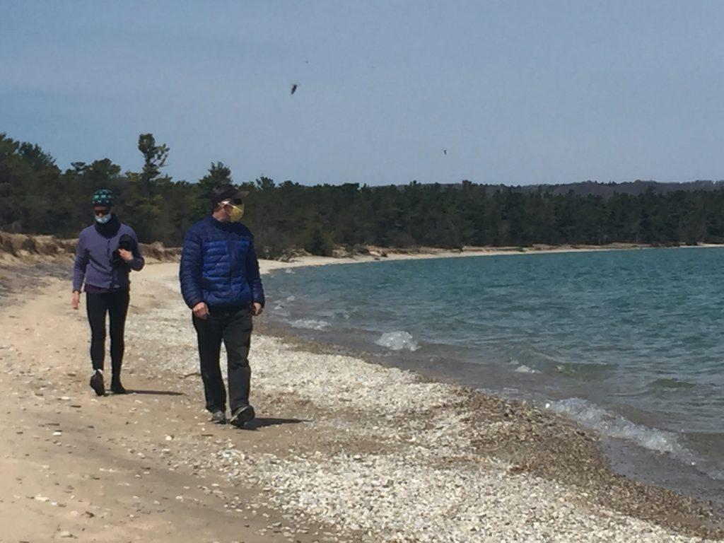 couple walking lakeshore with masks on