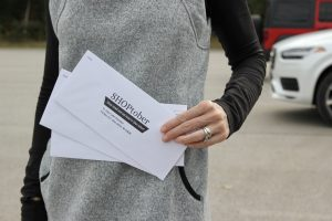 woman holding SHOPtober event envelopes